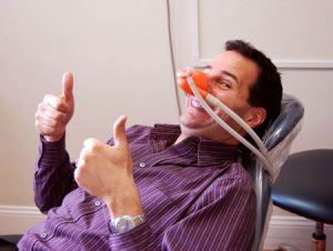 picture of man with a gas mask over his nose sitting in a dental chair smiling and giving two thumbs up