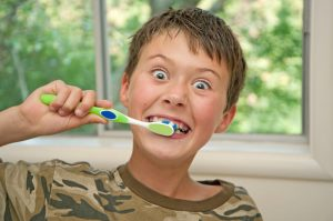 boy wearing a camo shirt brushing his teeth