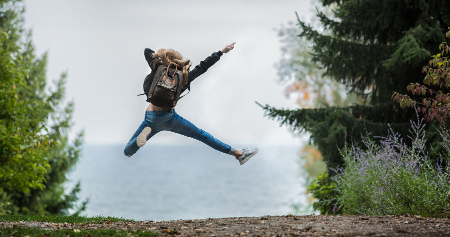 Blonde young woman wearing a backpack jumps next to a lake and forest