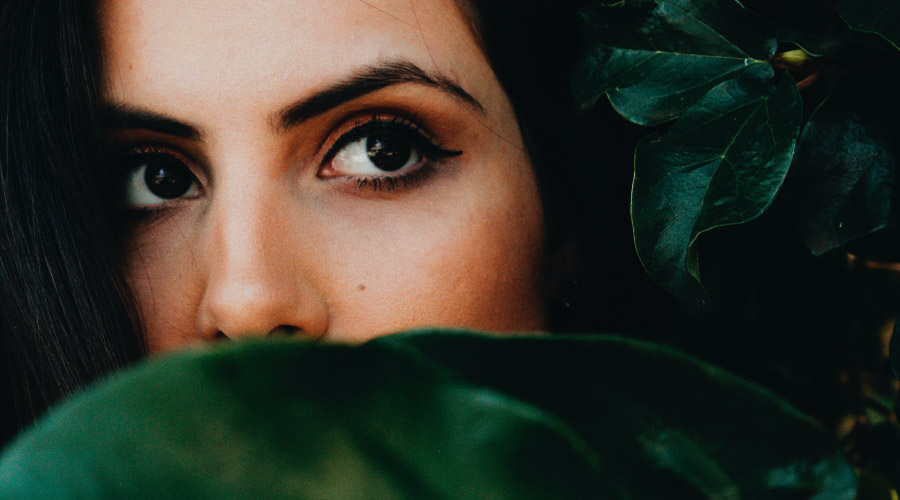 Closeup of brunette woman hiding her mouth behind a green leaf because she is concerned about bad breath
