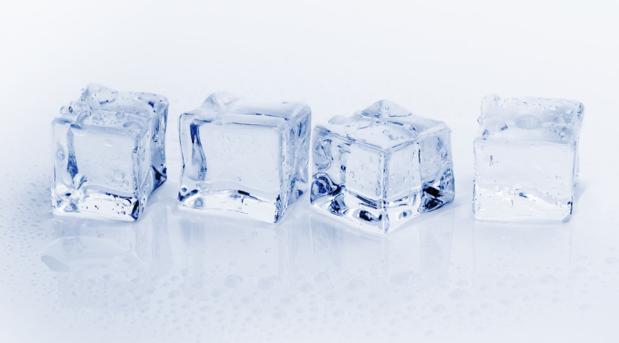 4 bluish-clear ice cubes, that could chip a tooth if chewed on, sitting on a white surface