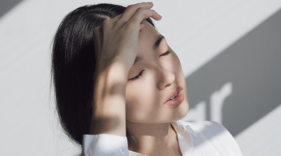 Closeup of a brunette woman wearing a white blouse and holding her hand to her forehead due to a headache